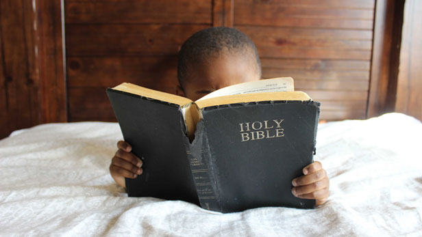 Young boy reading a well-worn Bible